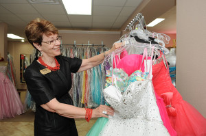 LAURA McKENZIE/Herald-Zeitung Connie Worley, owner of Celebrations, looks over some of her store's short prom dresses on June 1.