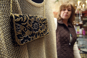 LAURA McKENZIE | New Braunfels Herald-Zeitung Susan Heflin holds an outfit with a matching purse with gold and silver beading available at Once in a Blue Moon Consignment and Resale Boutique on Dec. 11.
