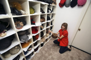 LAURA McKENZIE | New Braunfels Herald-Zeitung Marcia Kelly pulls out a few of the vintage hats in her collection on Thursday.
