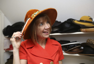 LAURA McKENZIE | New Braunfels Herald-Zeitung Marcia Kelly tries on her favorite hat in the collection on Thursday.